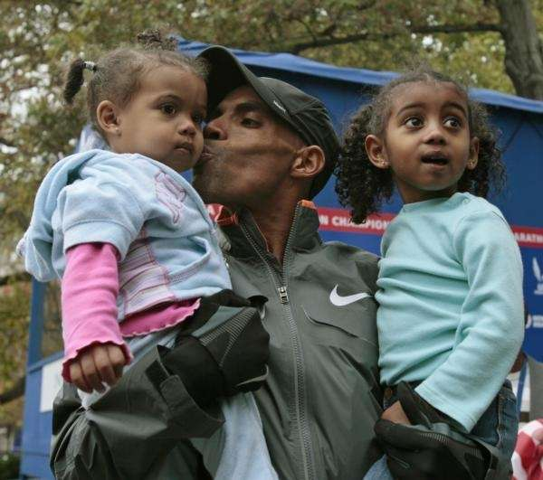Meb Keflezighi kisses his youngest daughter Fiyori, 1,