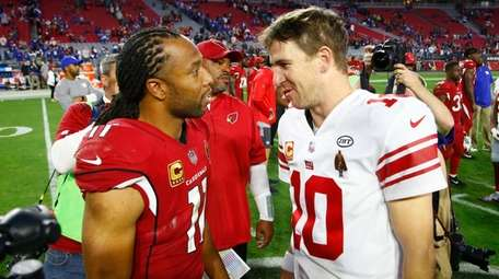 Cardinals wide receiver Larry Fitzgerald greets Giants quarterback