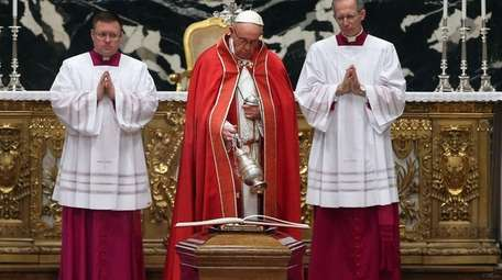 Pope Francis blesses the coffin of former Archbishop