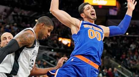 The Knicks' Enes Kanter falls after losing the