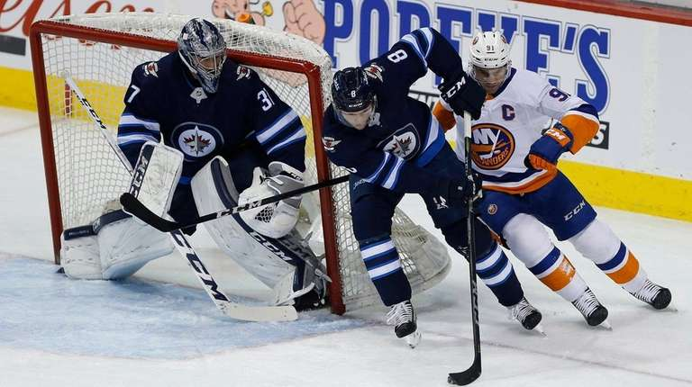 The Islanders' John Tavares chases the Jets' Jacob