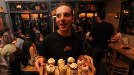Kevin Natoli serves a tray of desserts at