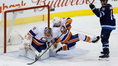 The Jets' Matt Hendricks checks Islanders' Ryan Pulock
