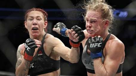 Cris Cyborg, left, hits Holly Holm during a