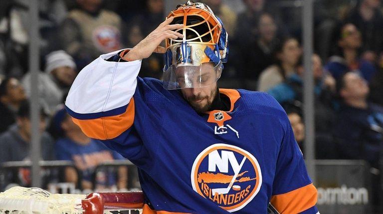 Islanders goaltender Jaroslav Halak pulls down his mask