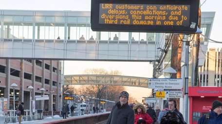 Commuters wait for a westbound train at the