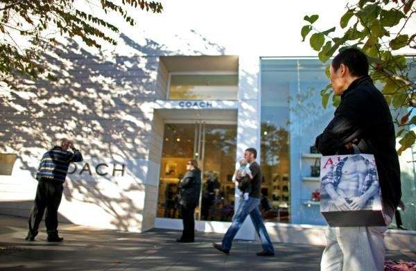 Shoppers walk with their shopping bags by the