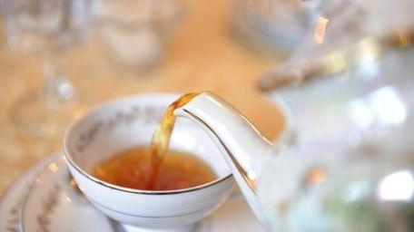 A waitress pours tea at Teapot, a newly