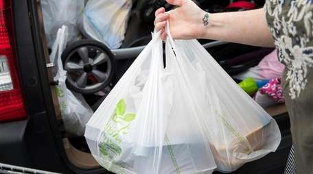 A woman loads her car with groceries from