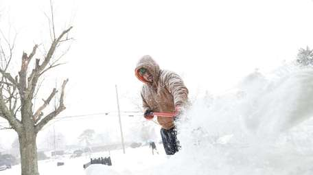 Alan Reibera shovels snow on Candlewood Road in