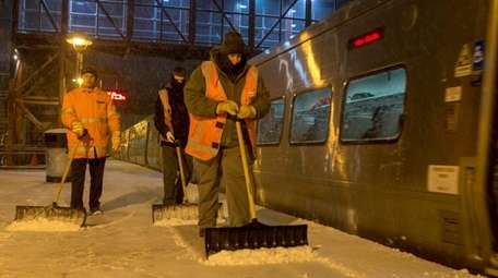 Workers clear snow from the platform at the