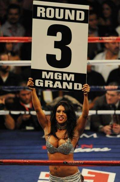 A showgirl holds up the round card during