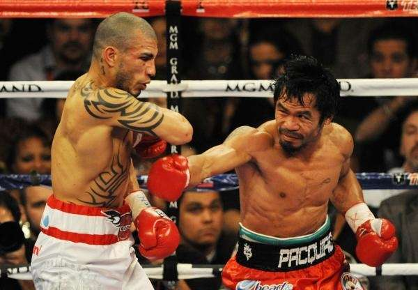 Miguel Angel Cotto of Puerto Rico (L) battles