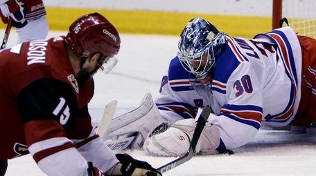 Rangers goaltender Henrik Lundqvist covers the puck in