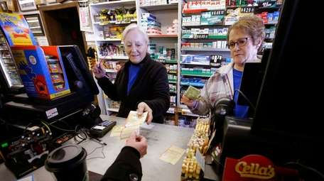 Cashiers sell a lottery ticket Sunday, Jan. 7,