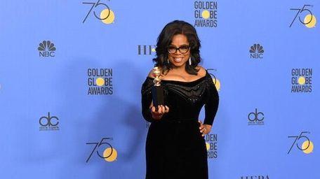 Oprah Winfrey holds her Cecil B. DeMille Award