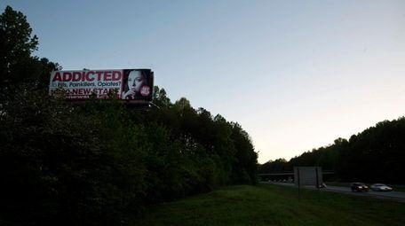 A billboard for a drug addiction service stands