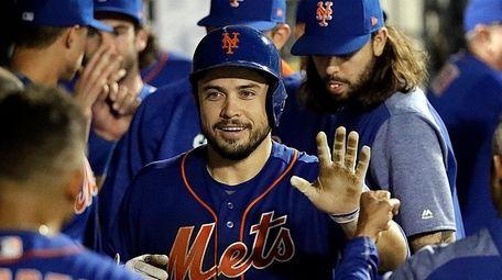 Mets catcher Travis d'Arnaud receives congratulations in the