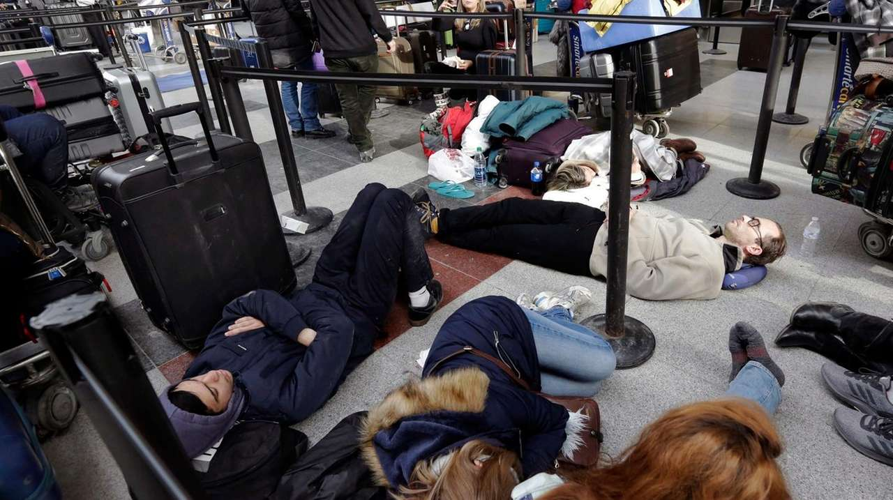 Tired Avianca passengers wait for flights at Kennedy