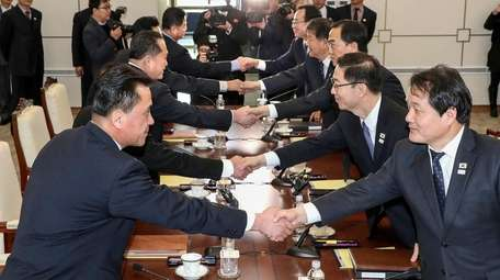 Members of the North Korean delegation, left, with