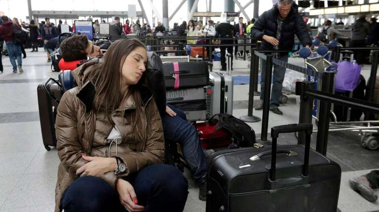 An Avianca passenger rests as she waits for