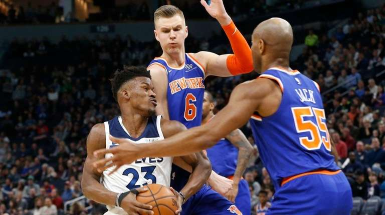 The Timberwolves' Jimmy Butler, left, tries to get