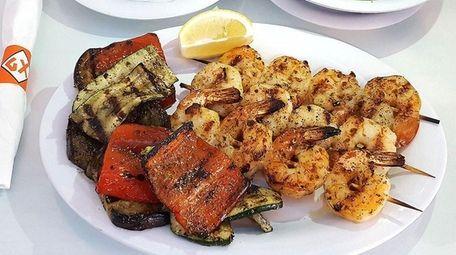 Shrimp kebabs are served with grilled vegetables at