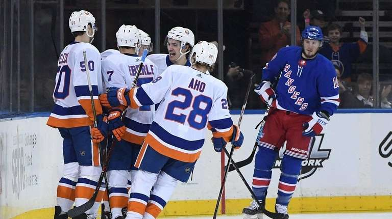 Islanders players celebrate a goal by center Anthony