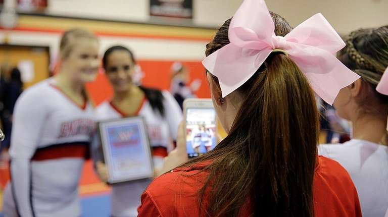 The Smithtown East varsity cheerleaders wore pink ribbons