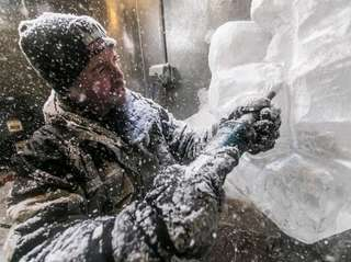 Ice sculptor Richard Daly makes detail cuts on