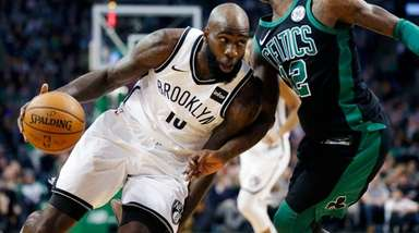 The Nets' Quincy Acy drives past the Celtics'