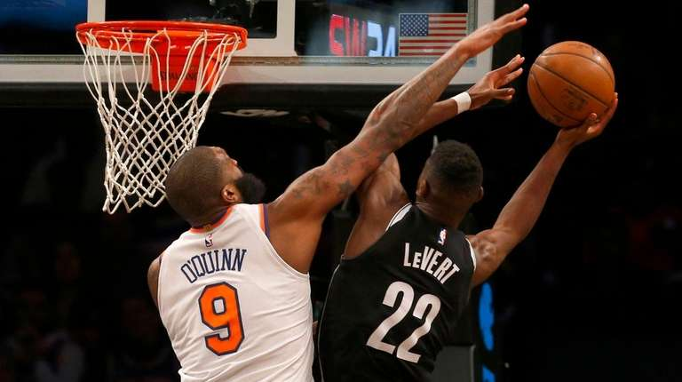Knicks center Kyle O'Quinn defends against Nets guard