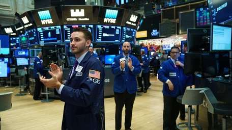 Traders applaud ahead of the closing bell on