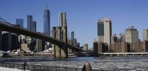 People look at ice floating along the East