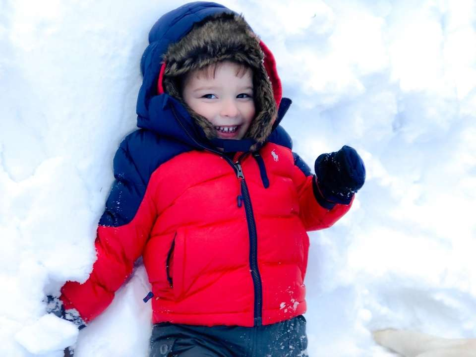 Vincent, 3, is all smiles making snow angels