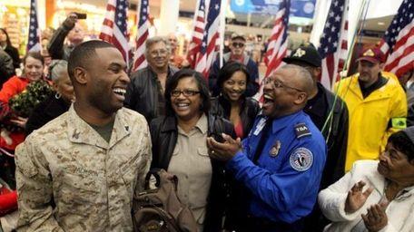 Marine Cpl. Lamarr Jackson laughs with his parents,