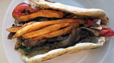 Fries adorn a pork gyro at Gyro Place,