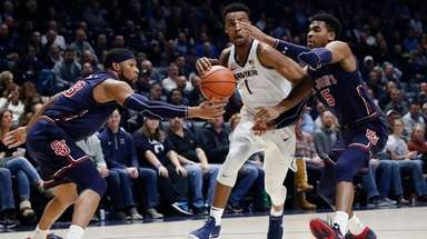 Xavier's Paul Scruggs drives against St. John's Justin