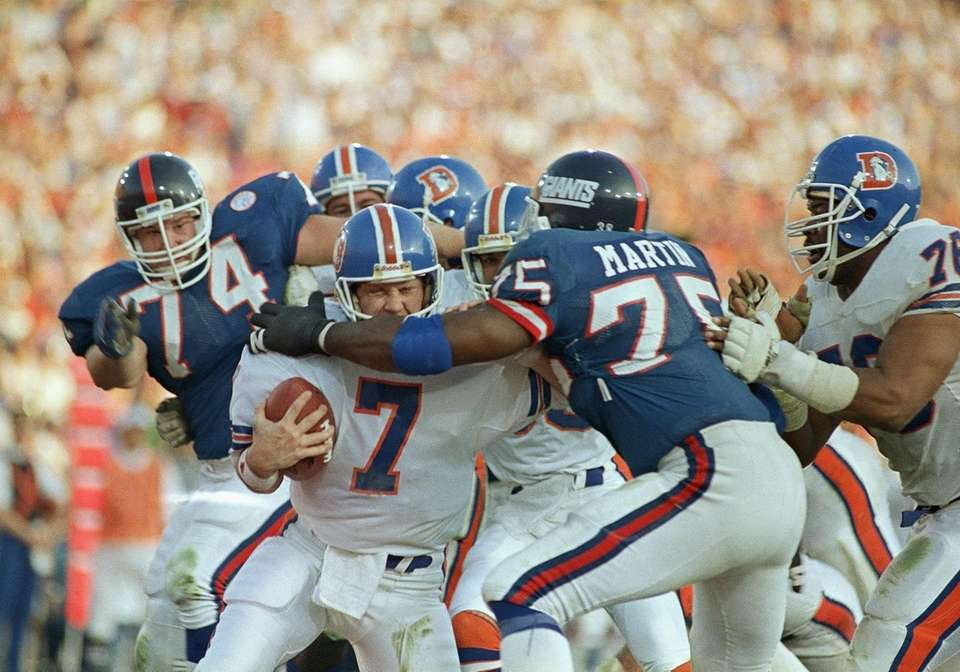 Denver Broncos quarterback John Elway gets sacked for