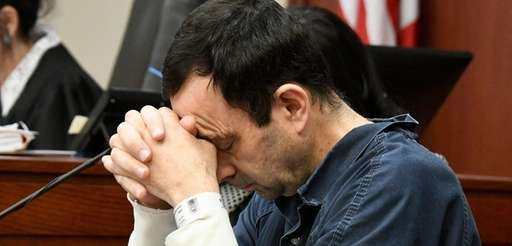 Larry Nassar puts his head down during a