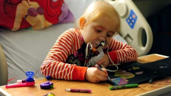 Six-year-old Julianna Buttner ignores the breathing apparatus she