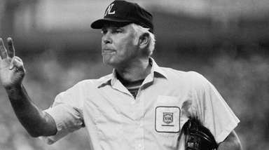 Plate umpire Doug Harvey gestures before play resumes