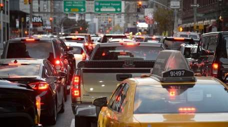 Cars wait on Sixth Avenue to enter the