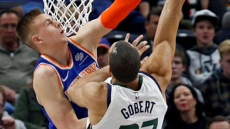 Knicks forward Kristaps Porzingis, rear, defends against Utah