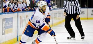 Josh Ho-Sang of the Islanders control the puck