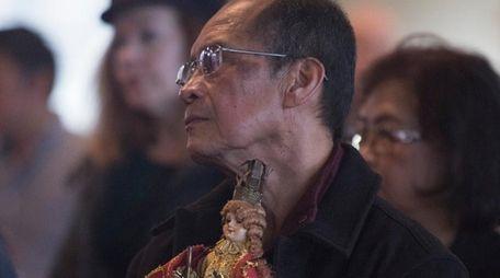 Frank Versoza, of Holbrook, prays during a celebration
