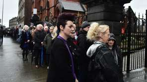 Mourners and the public wait in line to