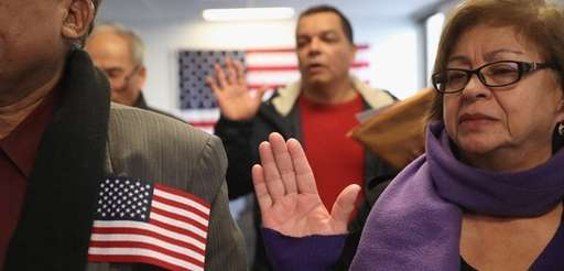 Immigrants take the oath of citizenship at a