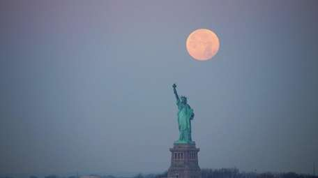 A supermoon sets behind the Statue of Liberty