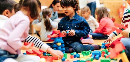 Group of children playing with blocks in kindergarten.